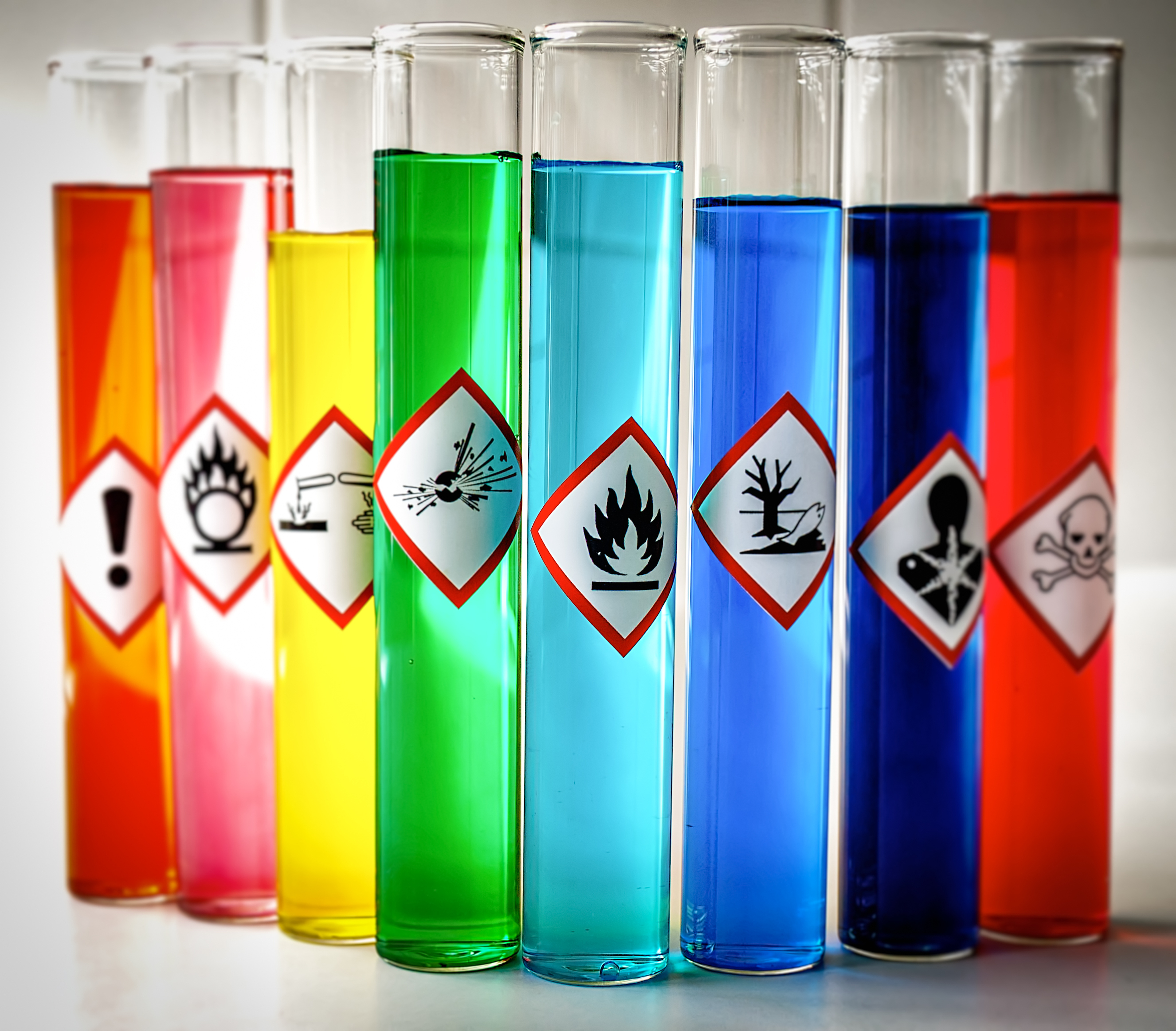 GHS pictograms on colorful liquids in test tubes_418194448